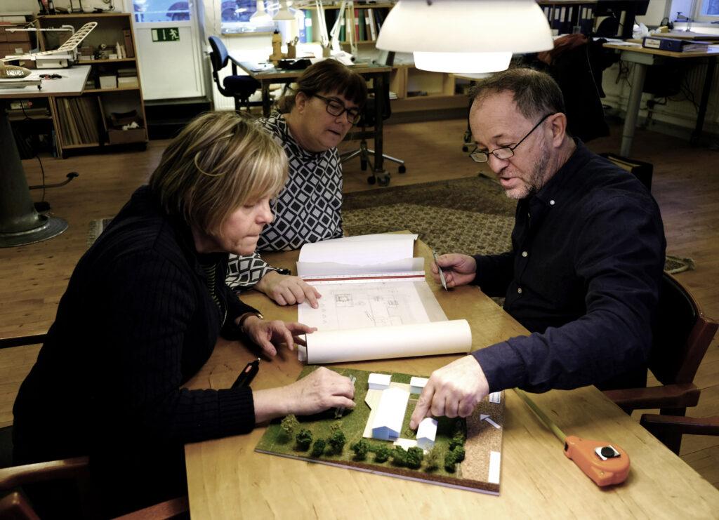 Per Qvarnström tillsammans med två klienter tittar på en modell